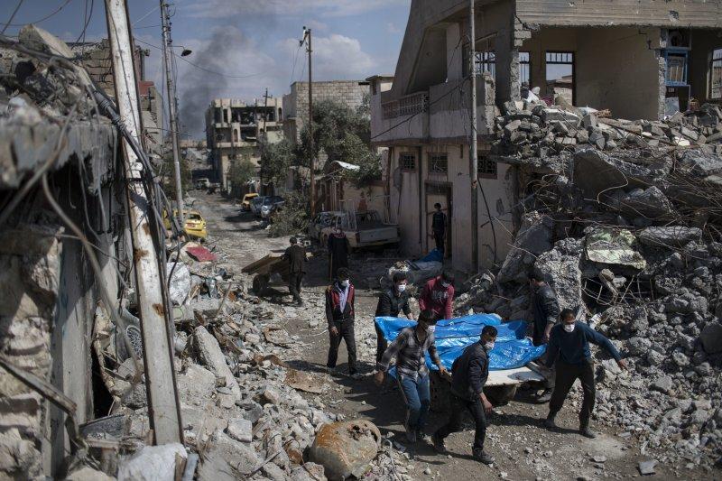 經過空襲後的摩蘇爾只剩斷垣殘壁,民眾忙著從瓦礫堆中搬出屍體。(美聯社)