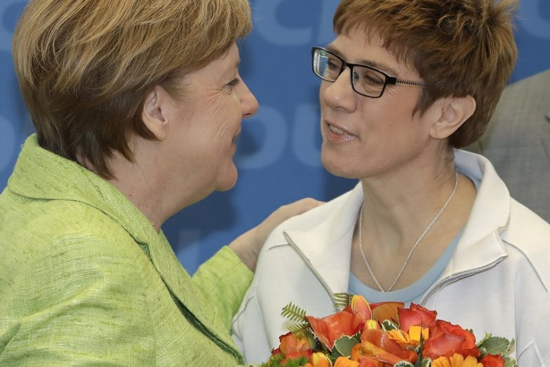 德國總理梅克爾27日微笑獻花給克朗普─卡倫鮑爾,恭喜她勝選(AP)