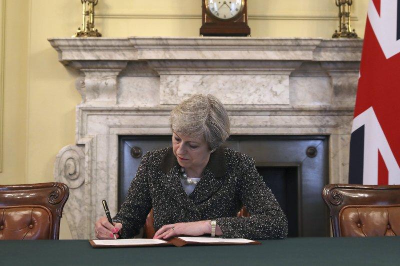 英國首相梅伊簽署脫歐通知書,29日下午送達歐洲理事會。(美聯社)