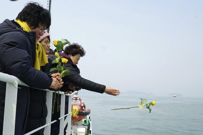 世越號失蹤者的家屬向大海投放悼念的花朵。(美聯社)