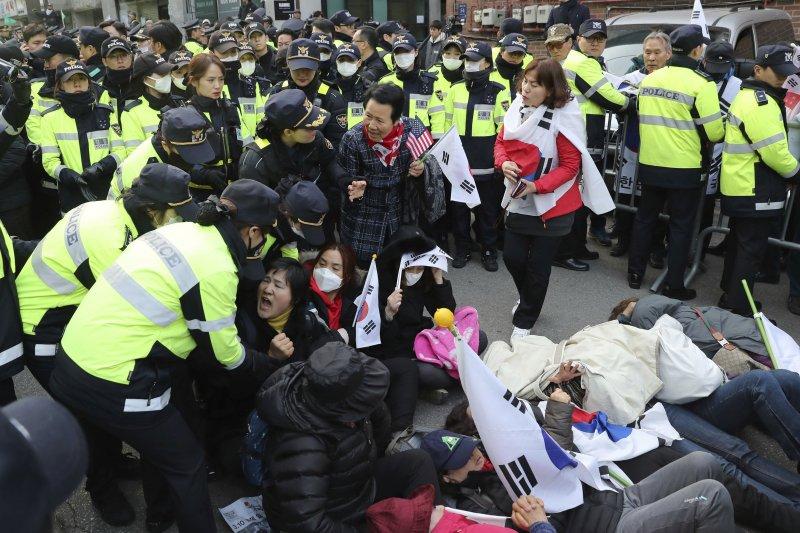 朴槿惠的支持者在三成洞的朴宅附近抗議,被優勢警力抬走。(美聯社)