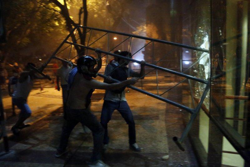 巴拉圭總統卡提斯(Horacio Cartes)企圖修憲取得連任資格,憤怒民眾3月31日移除國會外的拒馬,攻進議事廰。(AP)