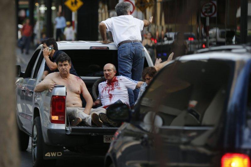 巴拉圭總統卡提斯(Horacio Cartes)企圖修憲取得連任資格,憤怒民眾3月31日攻進國會,一名參議員(左)被毆傷。(AP)