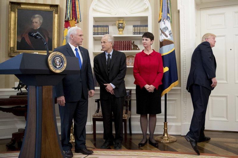 川普發表完談話就逕自開門打算走人,留下一屋子搞不清楚他為何不簽字的人們。(美聯社)