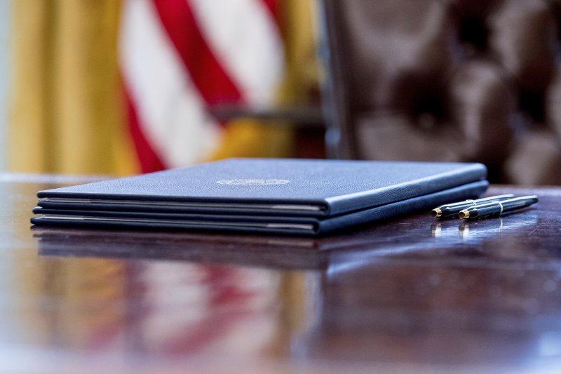 被川普遺留在桌上的兩份行政命令。(美聯社)