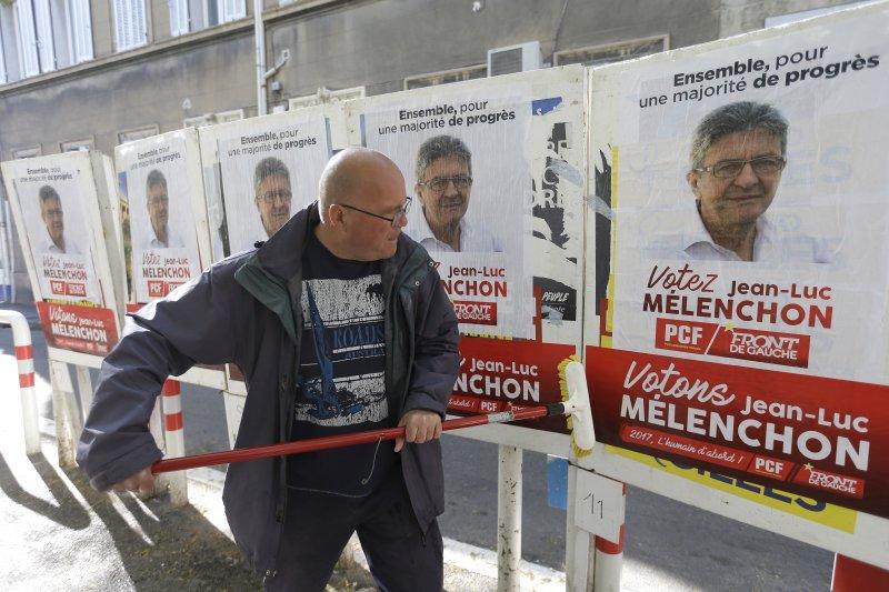 法國極左派總統候選人梅蘭雄的支持者正在張貼競選海報(AP)
