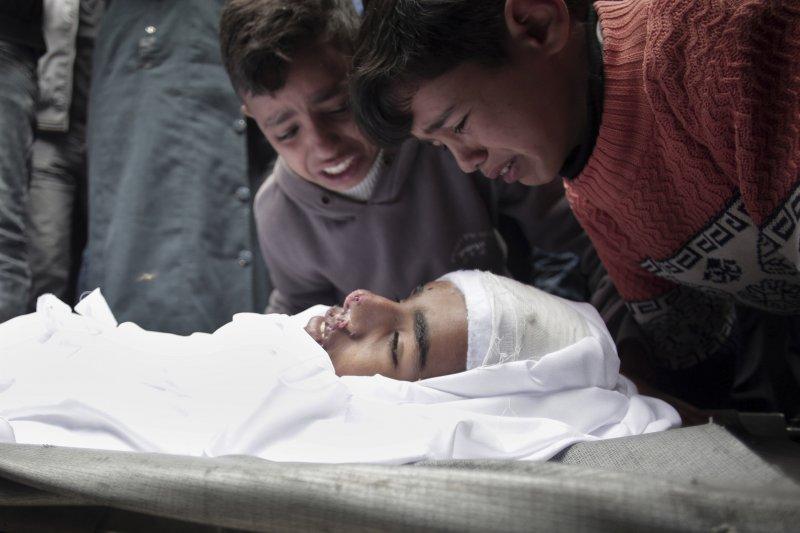 伊斯蘭國近日發動多起針對基督徒的攻擊,2名男童圍著罹難的18歲哥哥哭泣。(美聯社)