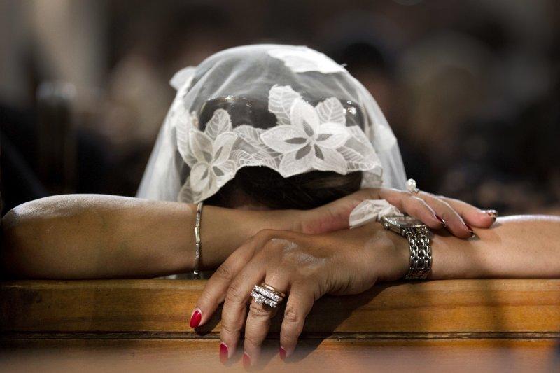 埃及科普特教堂被攻擊後,一名教徒在僅剩的椅子上禱告。(美聯社)