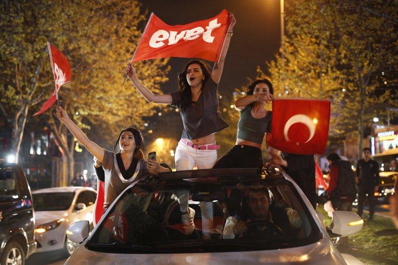 艾爾多安的支持者揮舞旗幟慶祝修憲公投過關。(美聯社)