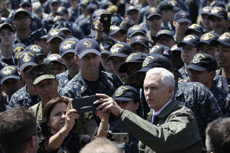 美國副總統彭斯登上雷根號核動力航母與官兵玩自拍。(美聯社)
