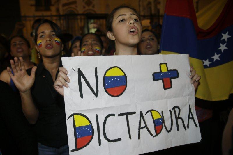 委內瑞拉民眾發起「示威之母」抗議行動,反馬杜洛民眾手持標語寫著「不要獨裁者」(AP)