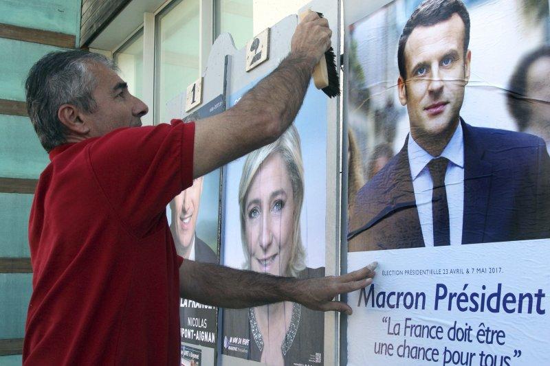 法國總統候選人馬克宏的支持者用馬克宏的海報蓋住另一位候選人勒潘的海報。根據選前的最新民調結果,勒潘與馬克宏最有可能在首輪投票中勝出(AP)
