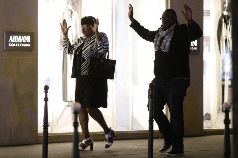 巴黎的香榭麗舍大道20日晚間發生恐攻後,民眾高舉雙手避免被誤認是恐怖分子。(美聯社)