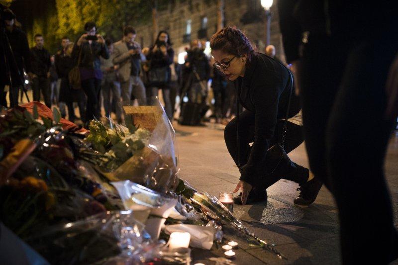 巴黎香榭大道20日晚間發生恐怖攻擊,一名員警殉職。隔天晚上,一位女子在該員警罹難處獻上鮮花(美聯社)