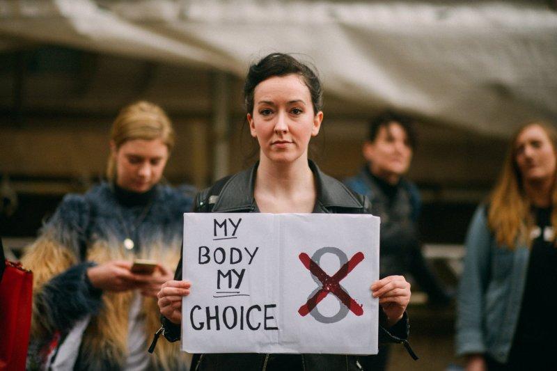 由愛爾蘭平民組成的「公民代表大會」(Citizens' Assembly)於22日以50比39票通過決議,建議國會以「修訂」的方式更改目前關於墮胎的憲法第8修正案。圖為一名抗議女子,手持「我的身體,由我決定」抗議標語。(取自London-Irish Abortion Rights Campaign臉書)