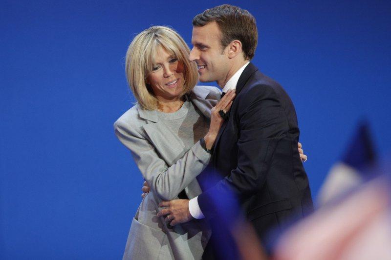 法國總統大選23日進行第一輪投票,中間派候選人馬克宏(Emmanuel Macron)在舞台上擁抱妻子布莉姬特(AP)