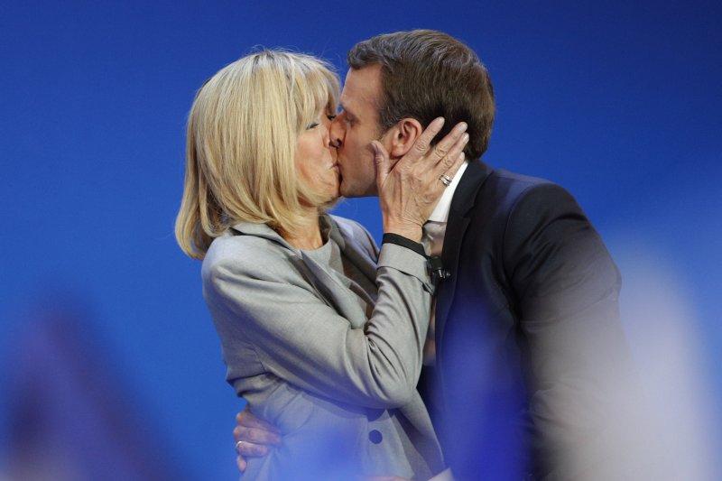 法國總統大選23日進行第一輪投票,中間派候選人馬克宏(Emmanuel Macron)在舞台上親吻妻子布莉姬特(AP)