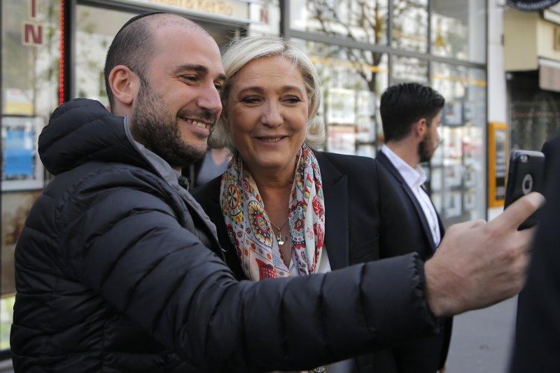 法國總統大選4月23日進行第一輪投票,極右派候選人勒潘勝出,與支持者合影(AP)