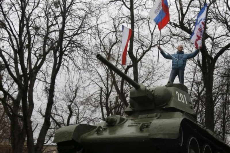 2014年2月,克里米亞舉行公投前夕,親俄的克里米亞民眾站在蘇聯時期的坦克上,揮舞俄國國旗與代表克里米亞的旗子(美聯社)