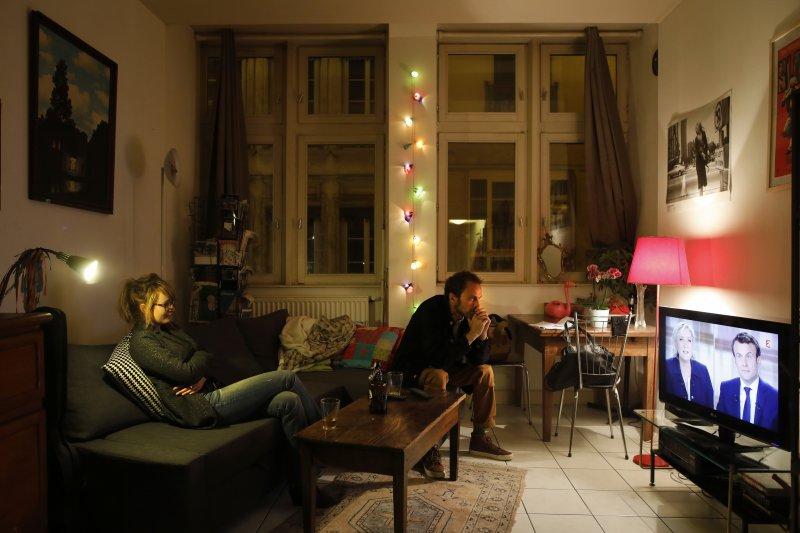 法國中部城市里昂的一對夫妻正在收看3日晚間的總統電視辯論(AP)