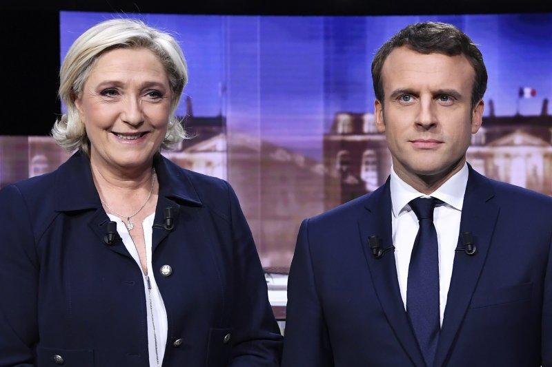 法國總統候選人馬克宏(右)與勒潘3日晚間舉行電視直播辯論,雙方火爆交鋒(美聯社)
