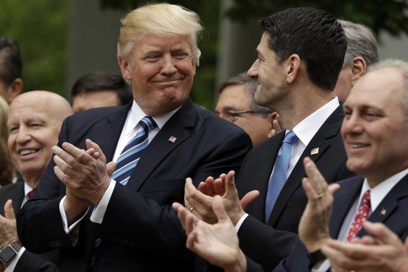 美國總統川普與共和黨力推的新版健保法案4日在眾議院闖關成功,為廢除歐巴馬健保跨出第一步,川普與議長萊恩相視而笑。(AP)