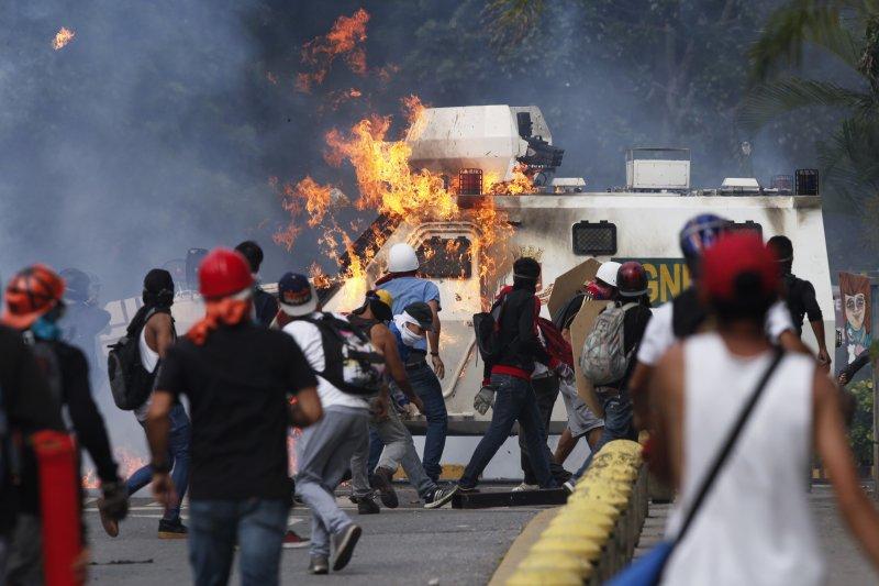 委內瑞拉的抗議者用汽油彈攻擊裝甲車。(美聯社)