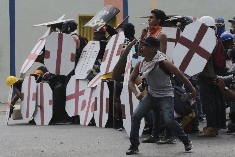 抗議馬杜洛修憲擴權的委內瑞拉民眾手持自製盾牌與警方頑抗。(美聯社)