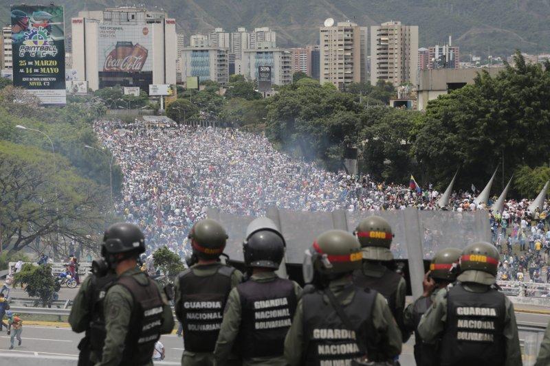 委內瑞拉的警察在高速公路上方監控湧向國會抗議的民眾。(美聯社)