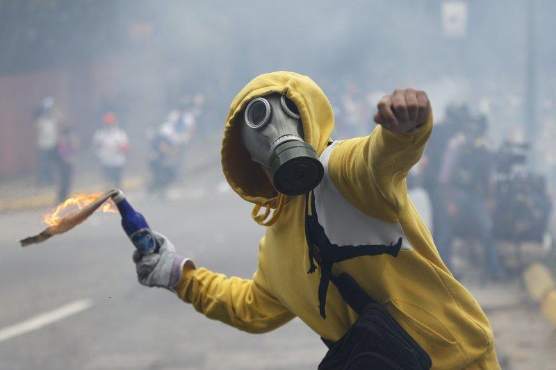 抗議馬杜洛修憲的委內瑞拉民眾在街頭丟擲汽油彈。(美聯社)