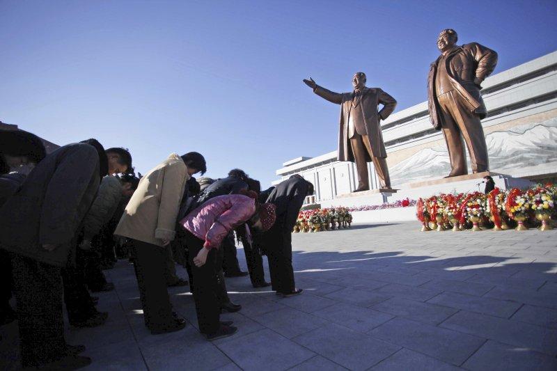 北韓民眾對前領導人金日成、金正日銅像鞠躬。(美聯社)