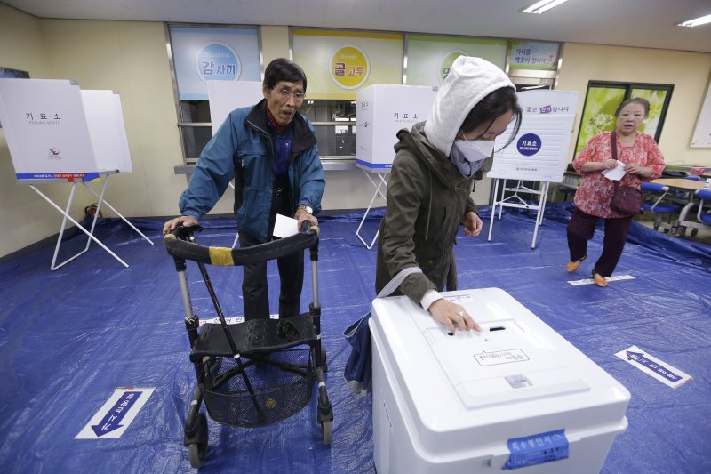 南韓民眾9日在投票所投票支持心目中的最佳候選人。(美聯社)