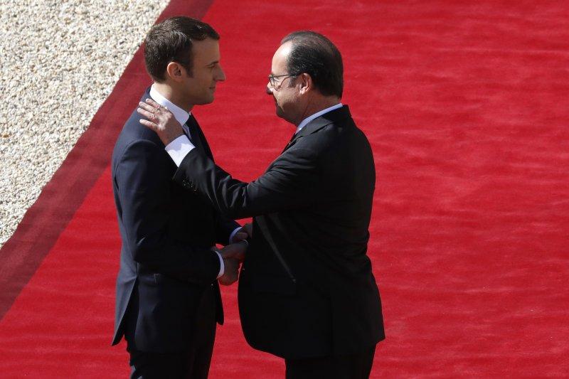 交棒,法國新任總統馬克宏(左)14日正式就職,卸任總統奧朗德與他寒暄(AP)