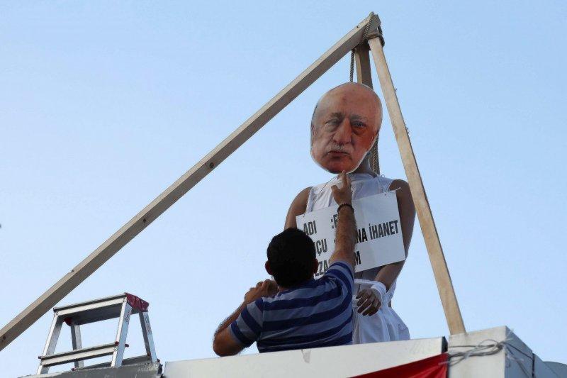 一名艾爾多安支持者將印有居倫的面具放在假人上,準備處死。(AP)