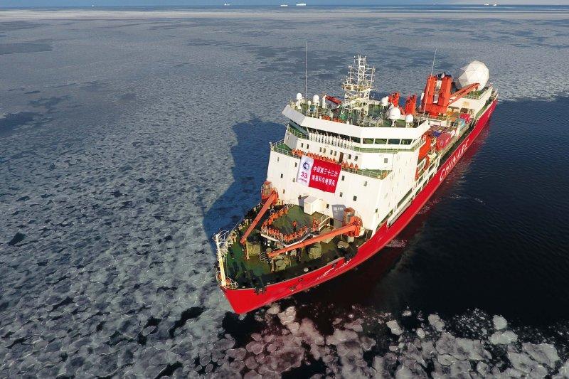 中國科考隊員在停泊於南極維多利亞地特拉諾灣的「雪龍」船上展開隊旗合影留念。(資料照,新華社)