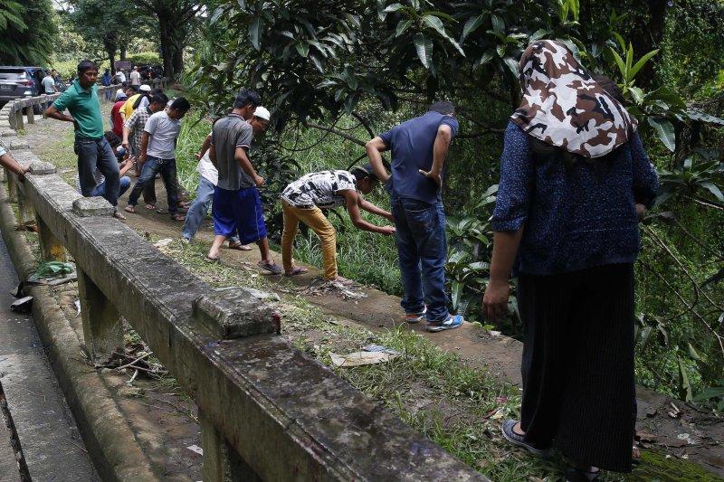 8名馬拉威市的居民被發現陳屍排水道,眾人正準備合力將遺體拉上來。(美聯社)