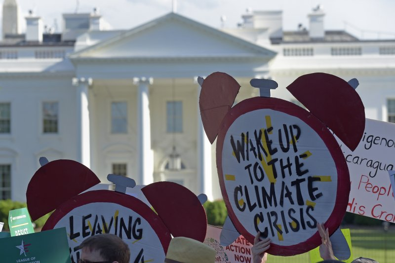民眾高舉「快醒來面對氣候危機」的標語,抗議川普退出《巴黎協定》。(美聯社)