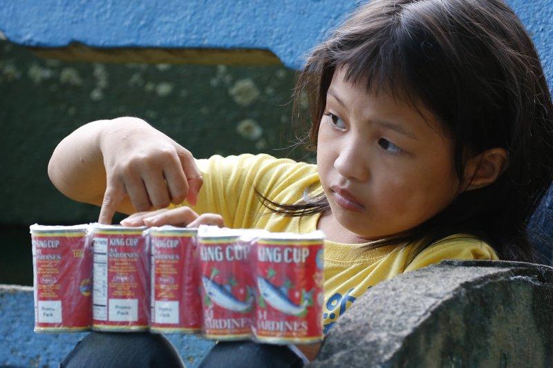 一位逃難的菲律賓女孩領到物資中心發放的沙丁魚,菲國政府軍正在南部的馬拉威與恐怖組織交火。(美聯社)