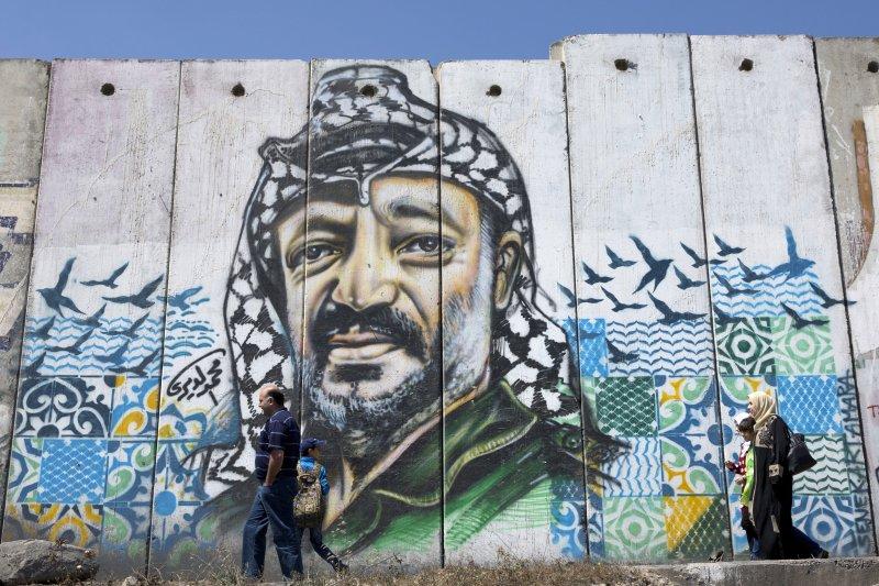 巴勒斯坦民眾走過以色列興建的「隔離牆」,上頭還畫著巴勒斯坦前領導人阿拉法特的肖像。