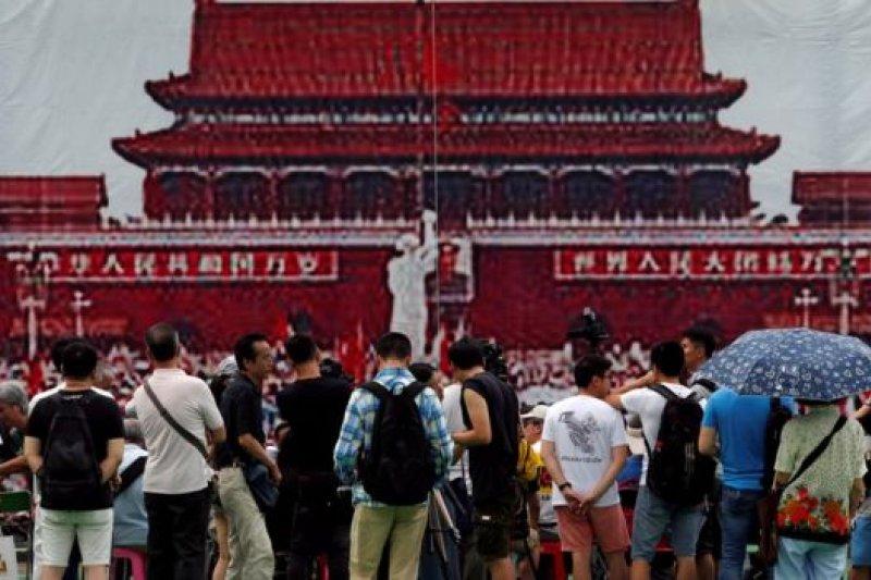 六四28週年晚會開始之前,維園群眾站在象徵1989年天安門廣場的海報前。(BBC中文網)