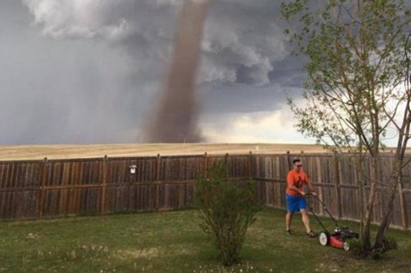 加拿大1名男子不顧後方龍捲風直竄天際,自顧自地悠閒除草。