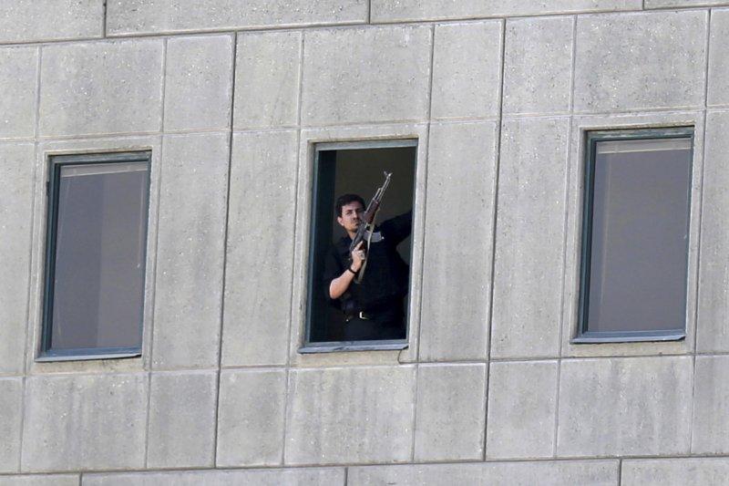 伊朗國會7日遭槍手闖入,媒體拍到拿槍靠在窗口的清晰兇嫌照。(美聯社)