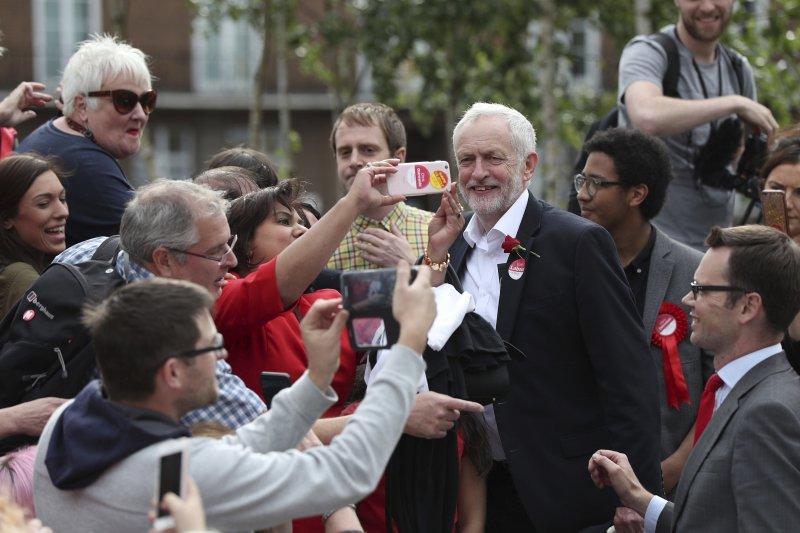 英國工黨黨柯賓作風親民,他親切地與支持者合照。(AP)