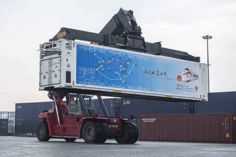 在中歐武漢班列起點、武漢鐵路集裝箱中心站內,一輛集裝箱起重機在往中歐班列上搬運貨物(新華社)