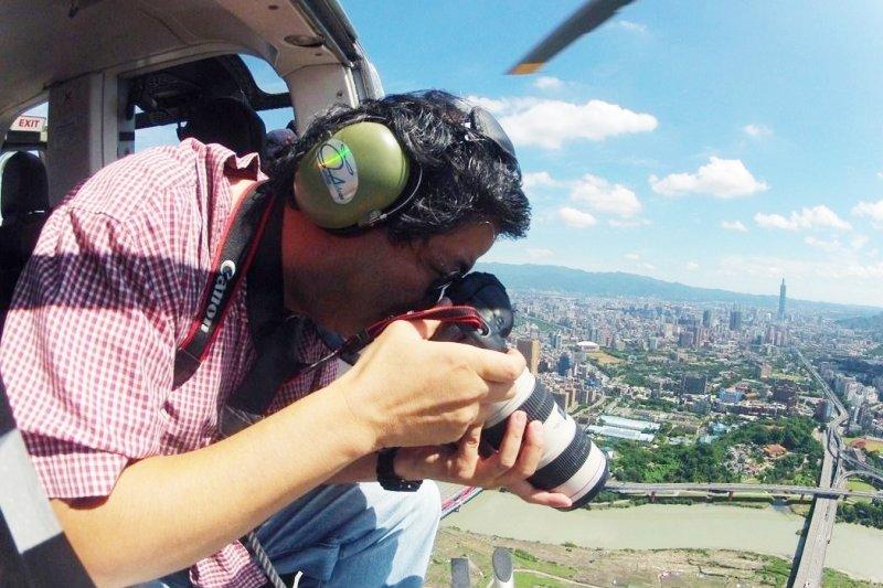 齊柏林導演在直升機上拿起相機空拍台灣土地。(圖片:台灣阿布電影公司;想想論壇提供)