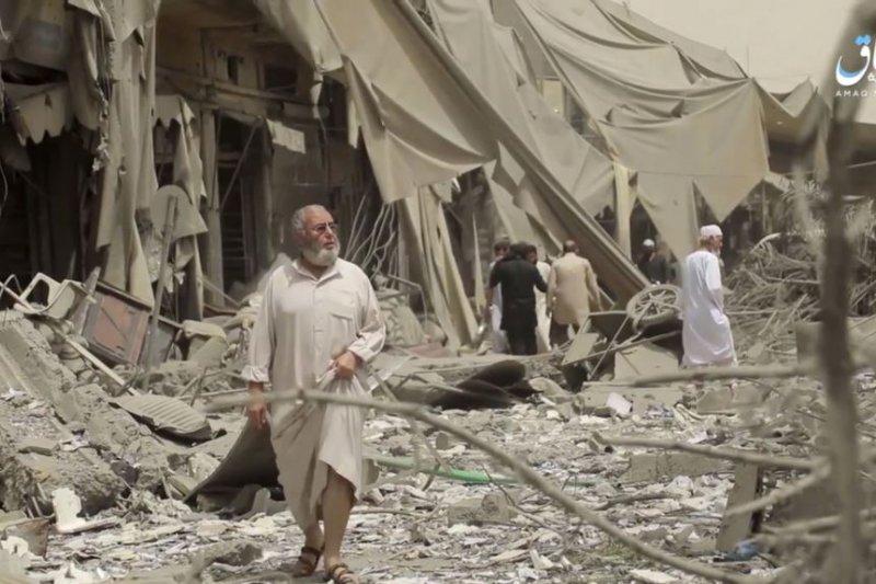 敘利亞城市拉卡居民在評估空襲造成的破壞。拉卡長期以來一直是伊斯蘭國的實際首都。(美國之音)