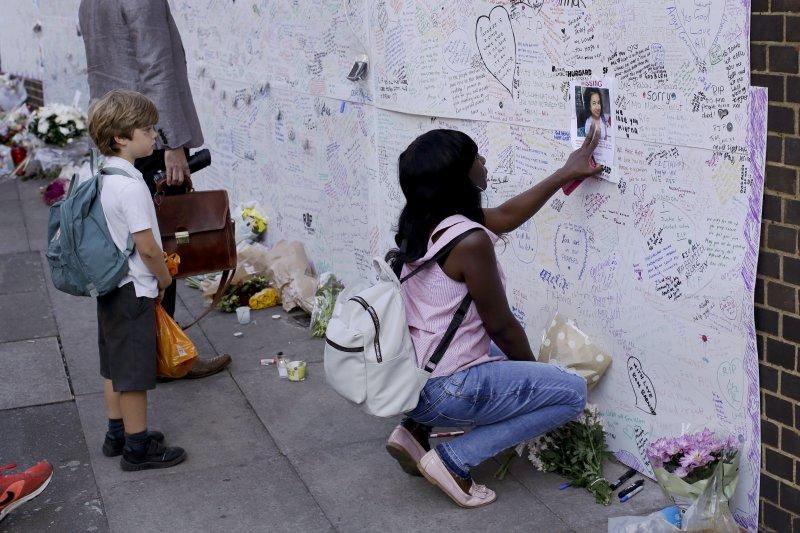 民眾悼念在英國格倫費爾大樓大火罹難和受傷的居民。(美聯社)