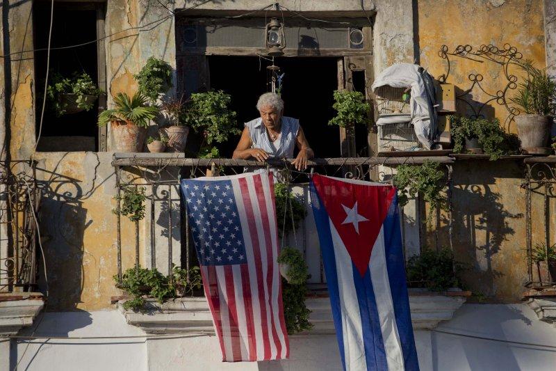 一名古巴民眾在陽台掛出美國與古巴國旗。(美聯社)