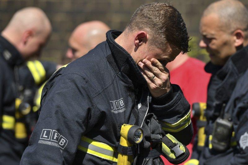 2017年6月14日,英國首都倫敦格倫費爾大樓(Grenfell Tower)發生大火,造成慘重死傷,消防員也黯然神傷(AP)