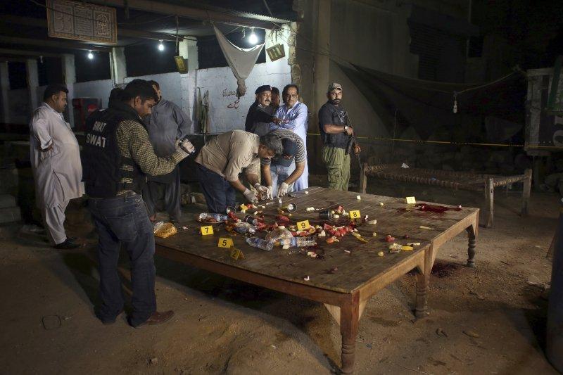 巴基斯坦的喀拉蚩23日發生一起襲警案,4名警察當街遭到槍手殺害,調查人員正在現場蒐證。(美聯社)